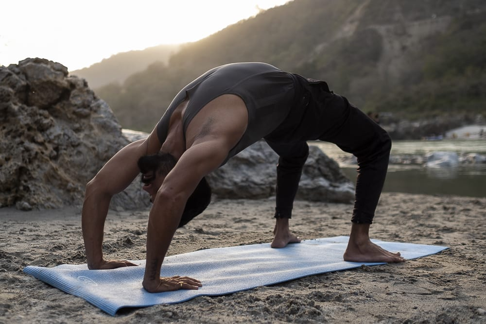 17 días haciendo un voluntariado en India, en la capital mundial del yoga: Rishikesh - Worldpackers - hombre haciendo yoga en Rishikesh en el río
