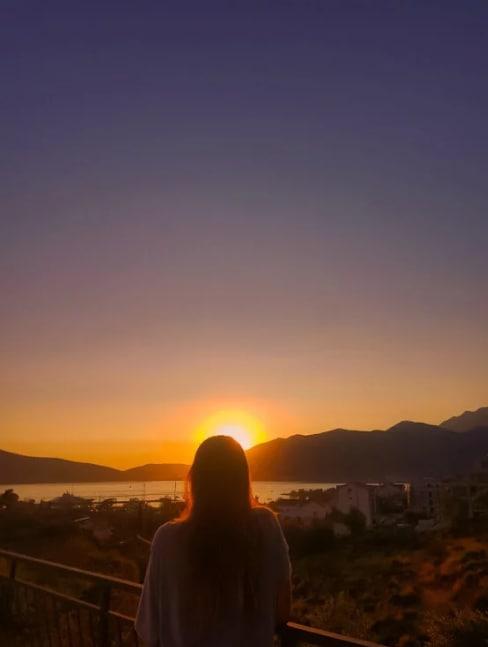 Stela vendo o pôr do sol em hostel que foi voluntária durante seu mochilão pela Europa