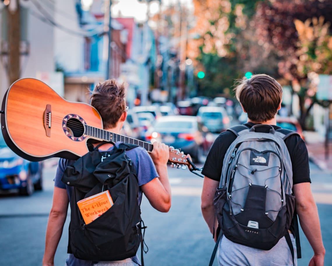 Imagem de dois garotos com mochila nas costas e um violão