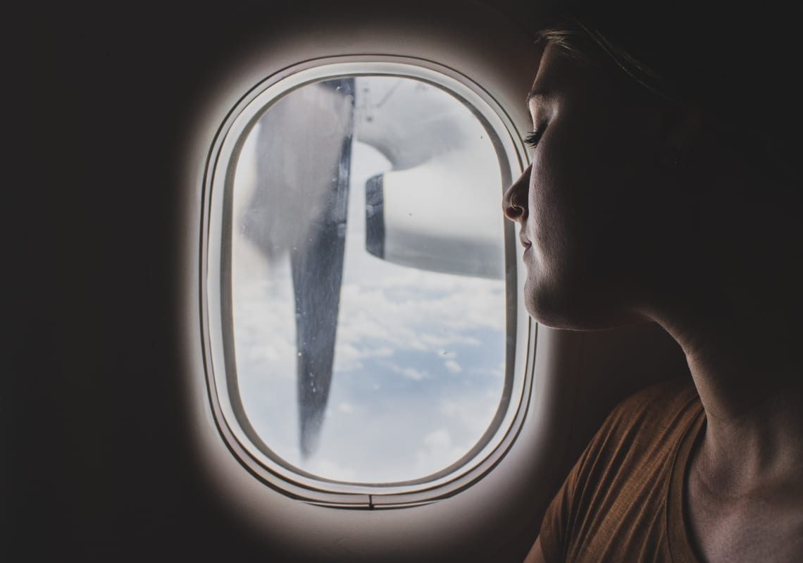 Female traveler looking out of airplane window