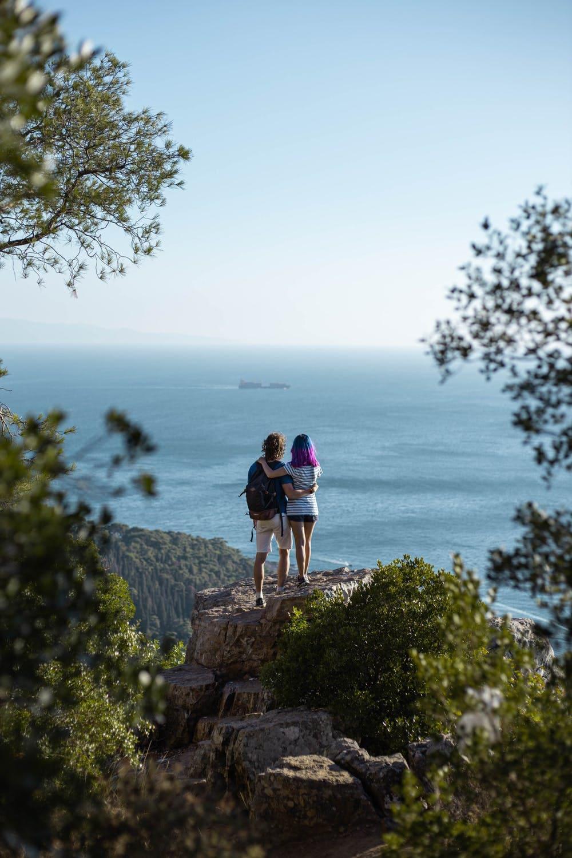 6 Lugares para viajar en pareja por Sudamérica y hacer voluntariados - Worldpackers - hombre y mujer mirando el horizonte sobre una piedra