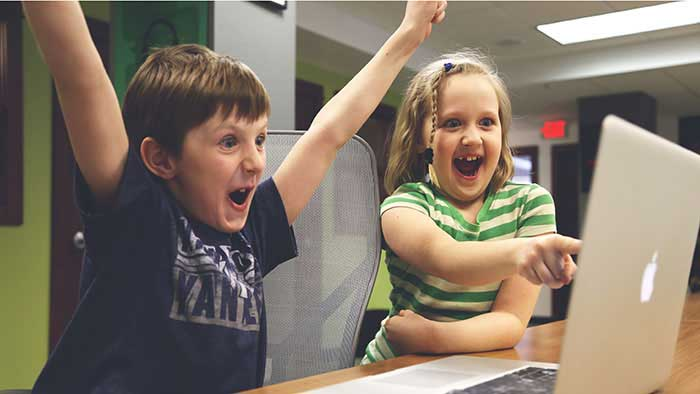 Two kids on the computer with winning excitement.