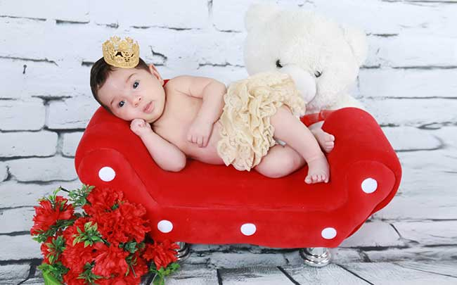 A baby is posing for the camera waiting for picture to be taken.