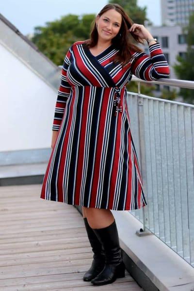 Frau in Wickelkleid mit roten Streifen und schwarzen Stiefeln