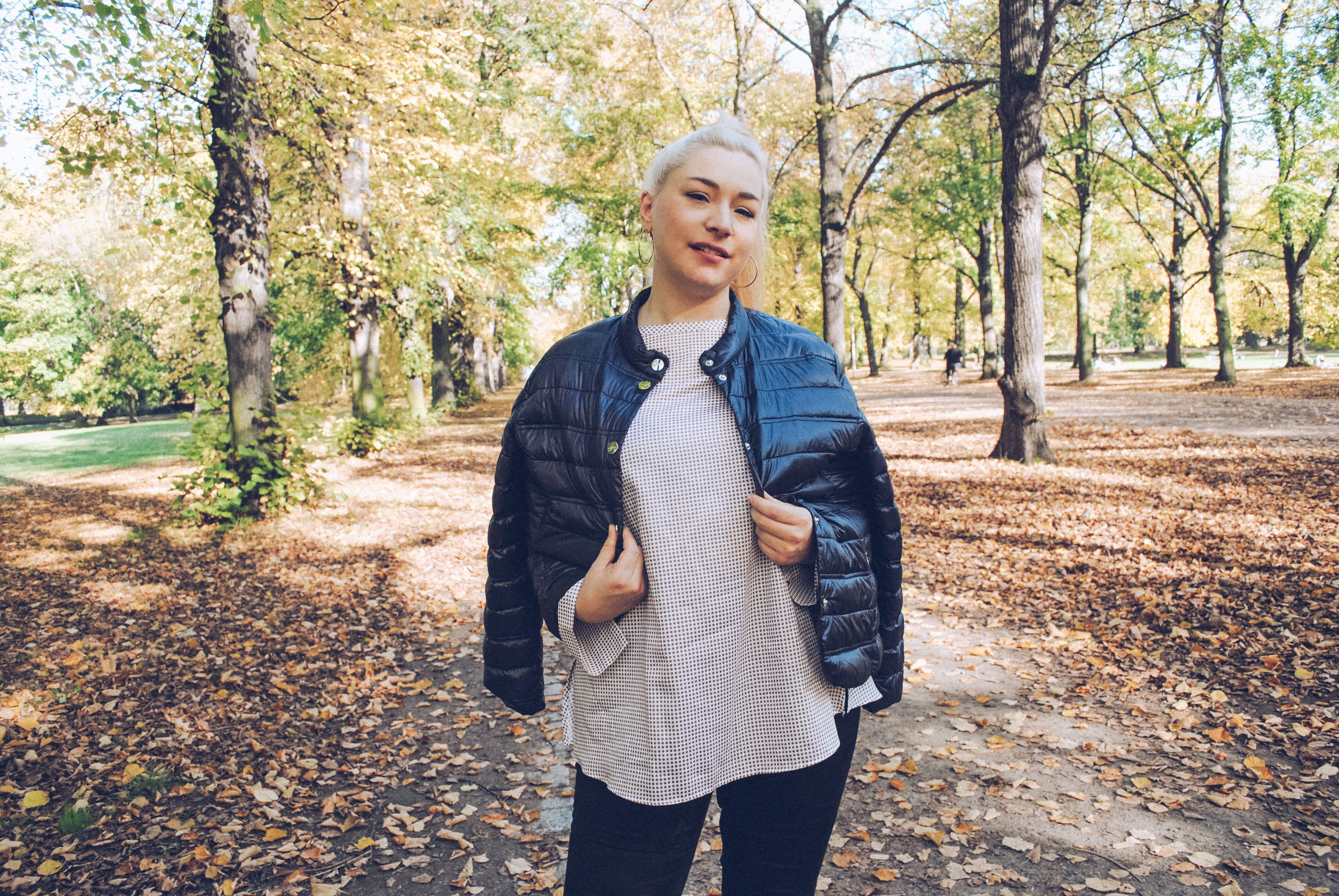 Blonde Frau in kurzer schwarzer Steppjacke
