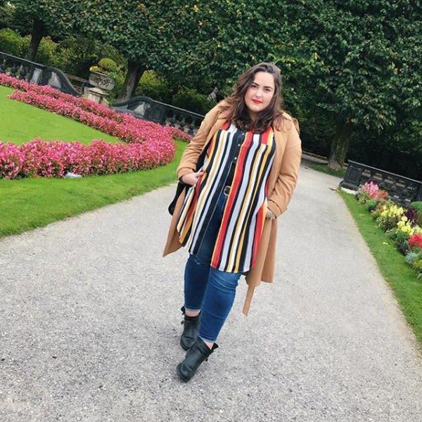 Junge Frau im langen beigen Mantel und Jeans