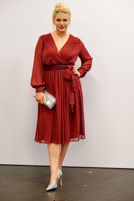 Frau in rotem Wickelkleid mit langen Ärmeln