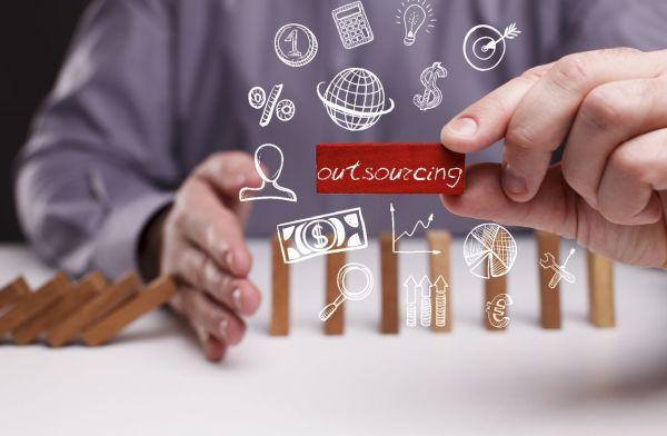 Imagen de una serie de dominos cayendo detenidos por una mano y una leyenda de íconos y la palabra Outsourcing