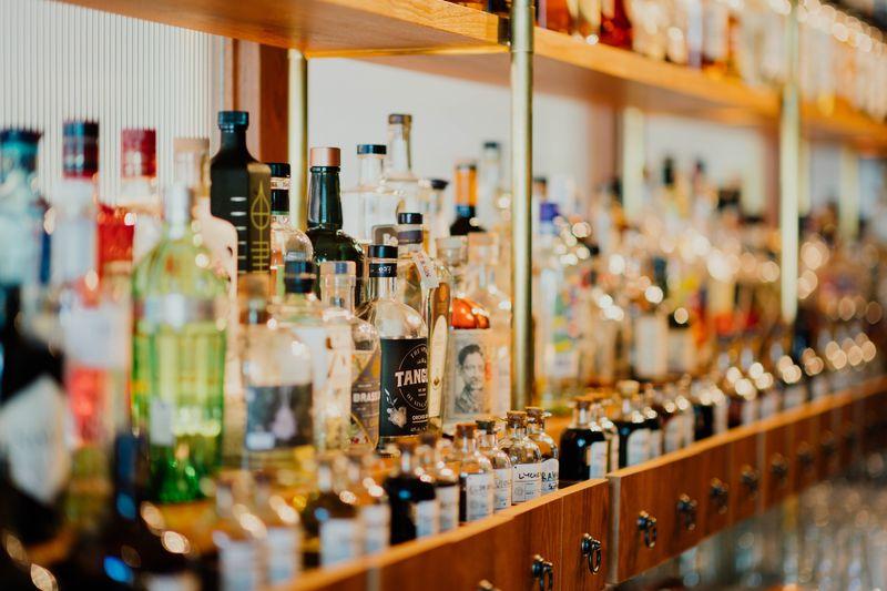 Foto de una estantería en una tienda de licor con rack de degustación