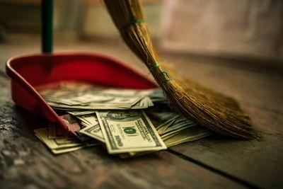 Foto-composición de una escoba barrendo billetes y subiéndola al recojedor de basura para el piso.