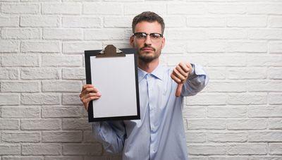 Foto de persona sosteniendo un tablero en señal de formularios manuales y apuntando con el dedo gordo hacia abajo en reprobación.