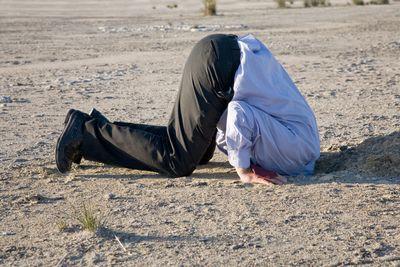 Foto de una persona en negación (con su cabeza metida en un hoyo en la pradera como el avestruz)