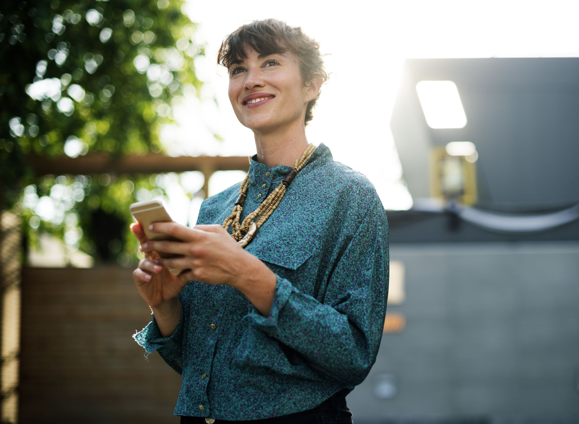 Businesswoman standing and using mobile phone hibob