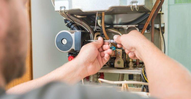 Technician adjusting a furnace