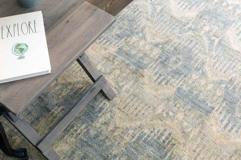 6x9' grey Ikat wool area rug in room under table with notebook