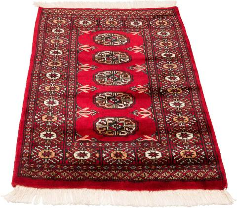 Angled image of red Bokhara rug looking over the pile giving it a lighter tone.