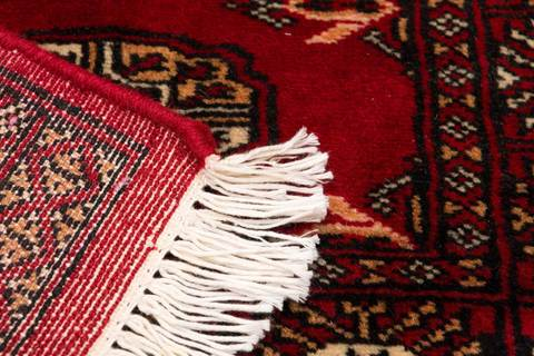 Detailed close-up image of red Bokhara's white fringe and back of rug.