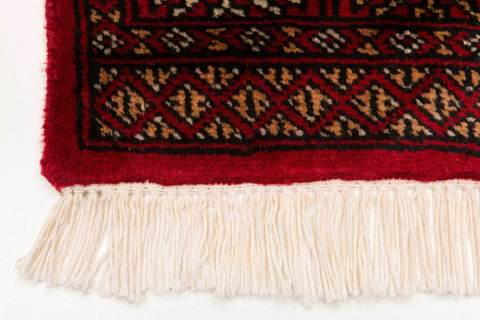 Detailed close-up image of red Bokhara's white fringe and corner showing detailed design at end of rug.