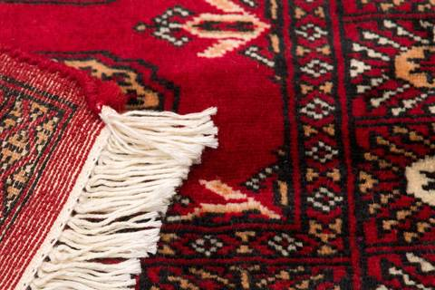 Detailed close-up image of red Bokhara's white fringe and back of rug on opposite end.