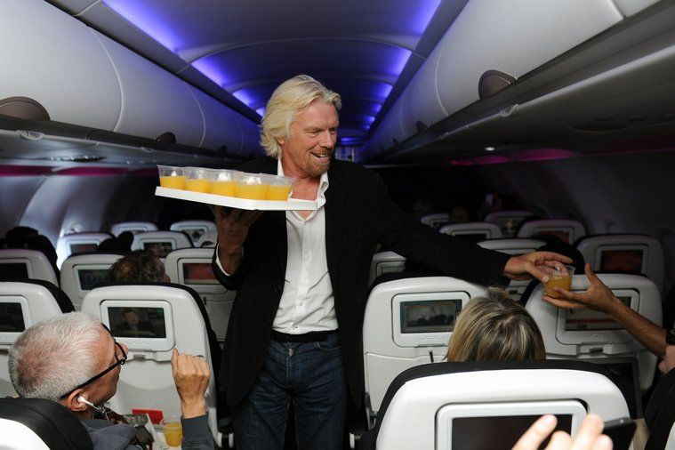 Richard Branson serving orange juice onboard Virgin America