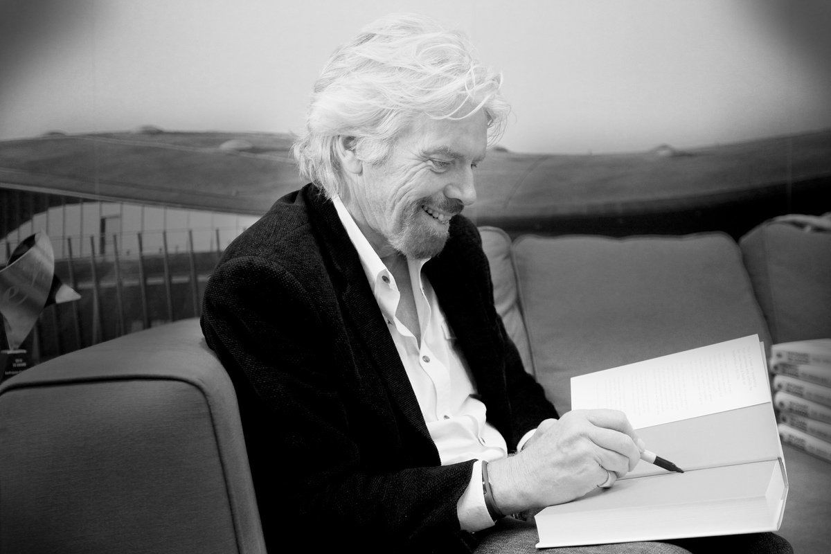 Richard Branson signing a book
