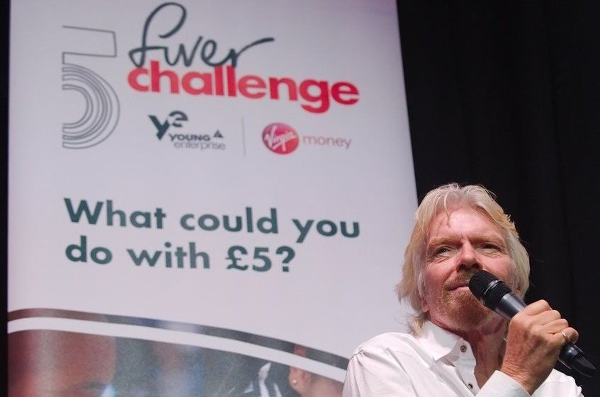 Richard Branson on stage with microphone at the Fiver Challenge