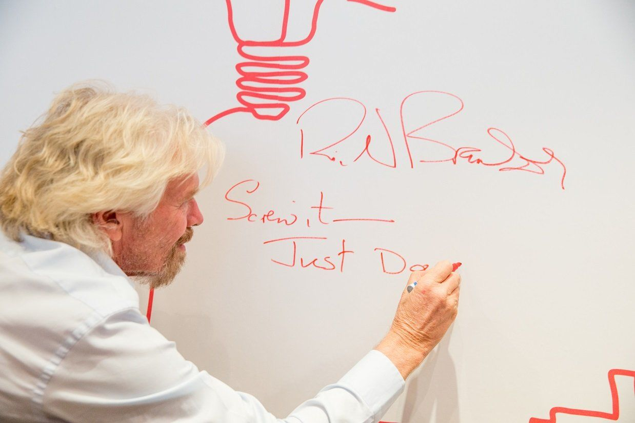 Richard Branson signing a wall