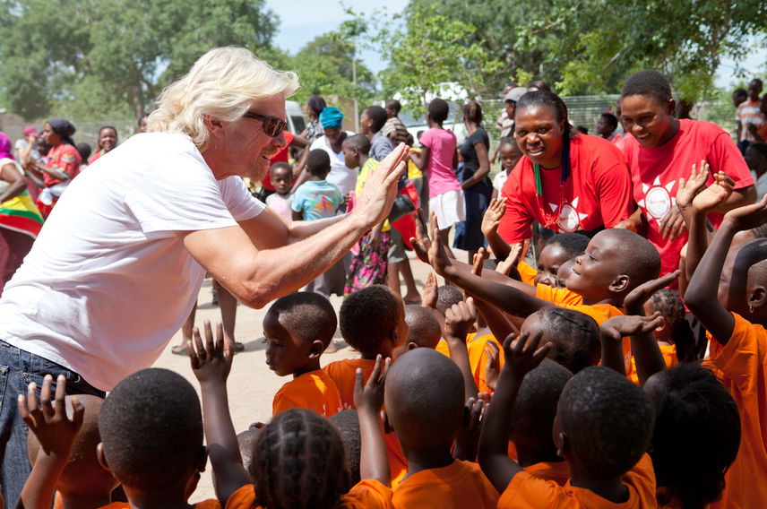 Richard Branson high five children in South Africa with Virgin Unite