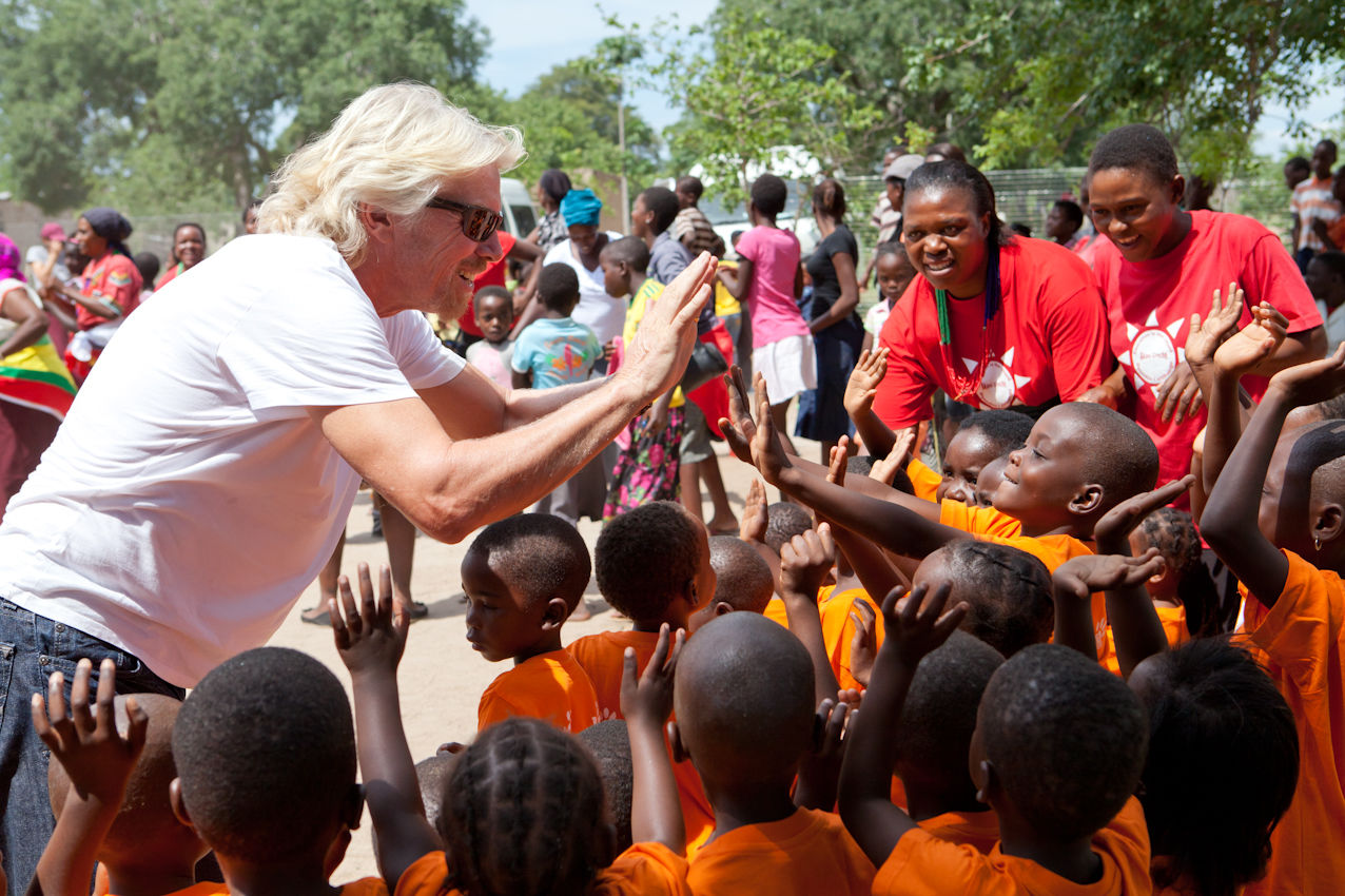 Richard Branson high five children in South Africa with Virgin Unite