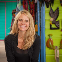 A portrait of a smiling Jean Oelwang with a vibrant background taken in Jamacia