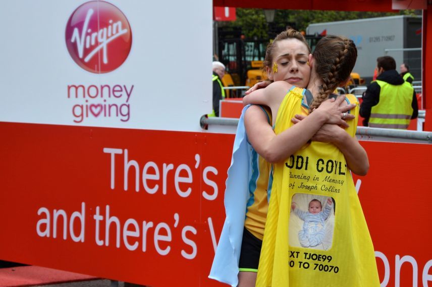 Charity runners embrace at the end of the 2015 Virgin Money London Marathon