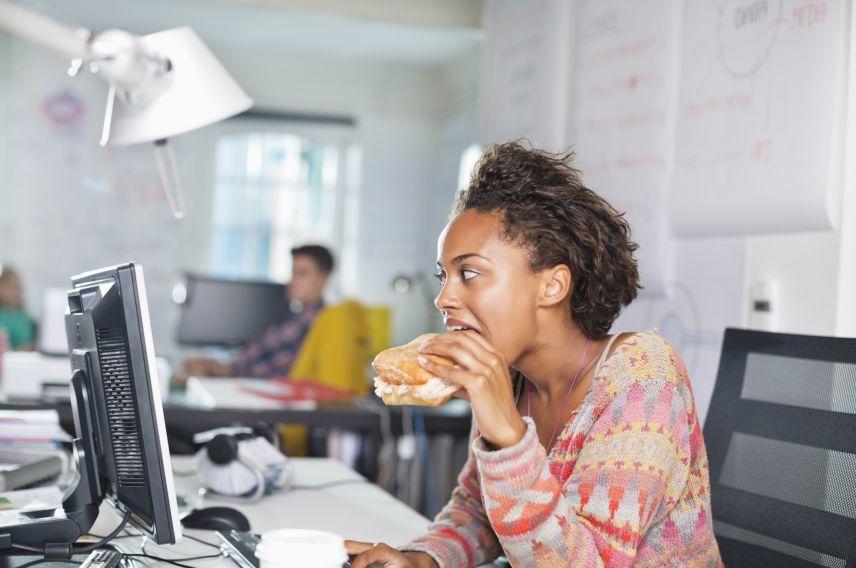 Woman eating burger at desk