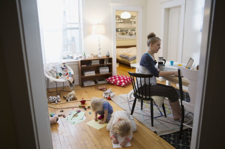 Mother working while children play