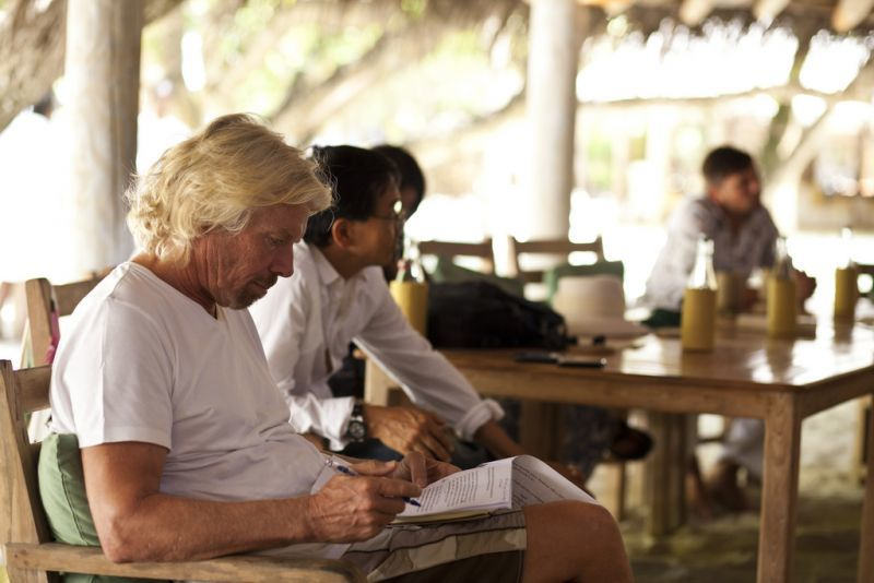 richard branson reading with a pen