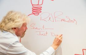 Richard Branson signing a wall