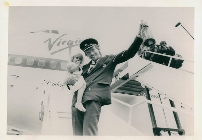 Richard holding his daughter Holly as he celebrates launching Virgin Atlantic