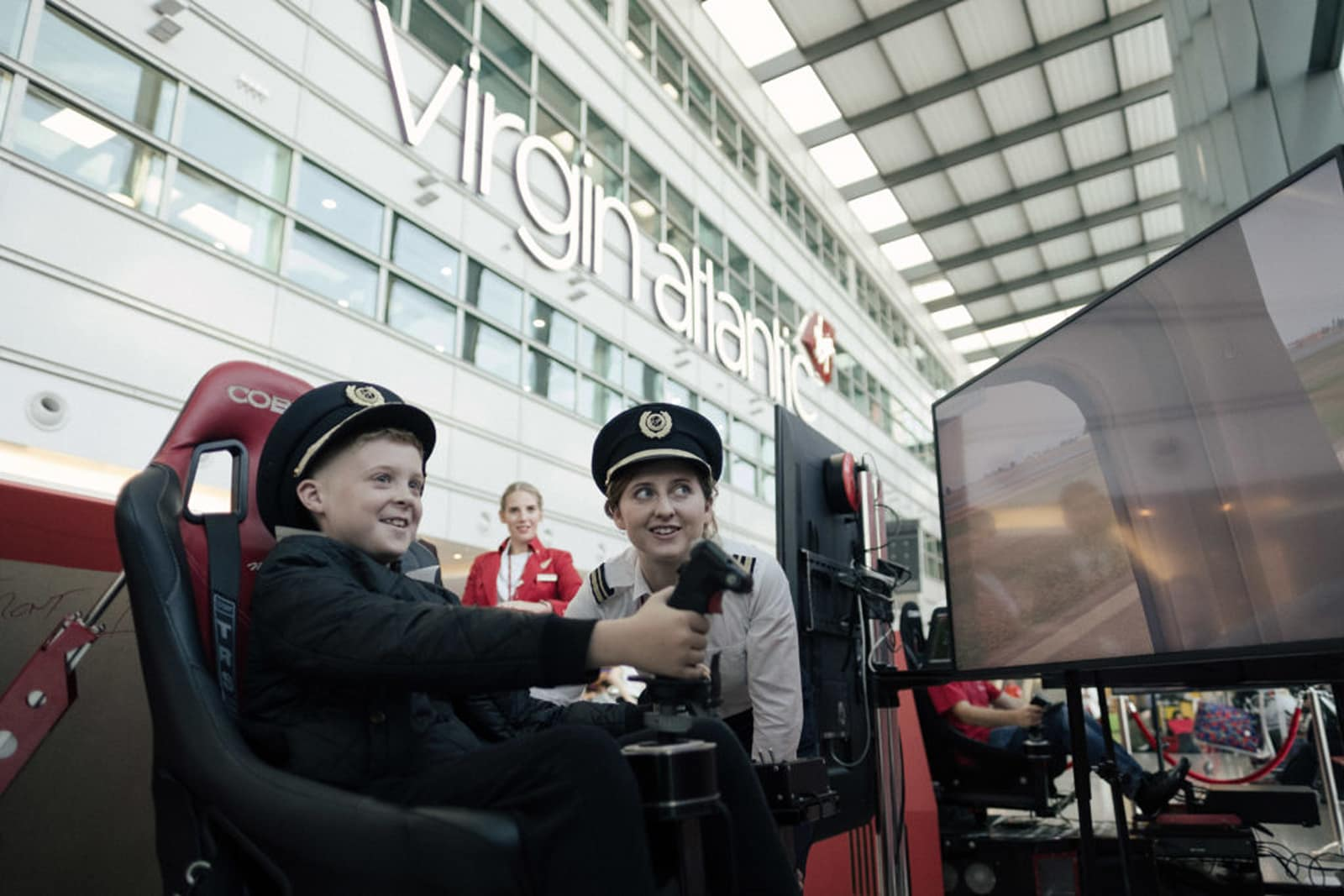 Child trying out flight simulator while Virgin Atlantic pilot and crew member look on