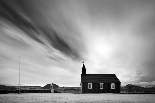 Budir Church, Snaefellsness Peninsula, Iceland. Visiting this iconic location in Iceland I noticed the clouds had left a pattern around the church spire. I composed this image to present the scene as if a beam was coming out of the church. Canon 5D Mark II converted to 720nm infrared, Canon TS-E 17mm f/4L, 1/30 sec @ f8, ISO 100, tripod. Monochrome conversion and curves adjustments in Photoshop CC.