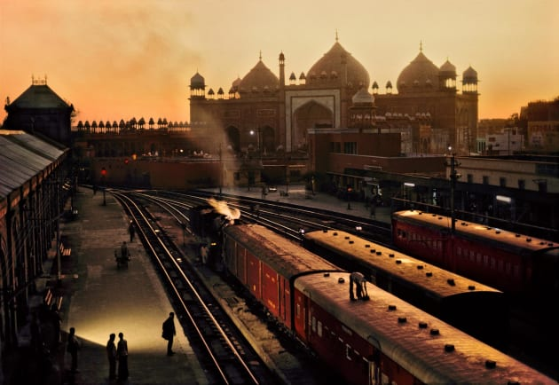 Train Station, Agra, India, 1983. In this shot McCurry has captured Agra's train station during the 'golden hour'. Originally this was a term used by cinematographers to denote that time of day when the setting or rising sun casts everything in a rich golden light. It's a quality that brings an opulence to a scene. Copyright Steve McCurry.