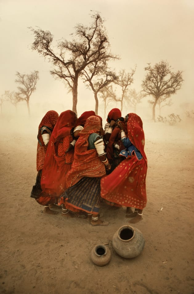 "Dust storm, Rajasthan, India, 1983. McCurry once said, ""You can't get hungup on what you think your ""real"" destination is. The journey is just as important."" The evidence of his attitude was amply realized when he was driving along a highway in Rajasthan, India. He was stopped for a while by a dust storm and he captured the moment a group of workers were protecting each other from the choking dust. Copyright Steve McCurry."