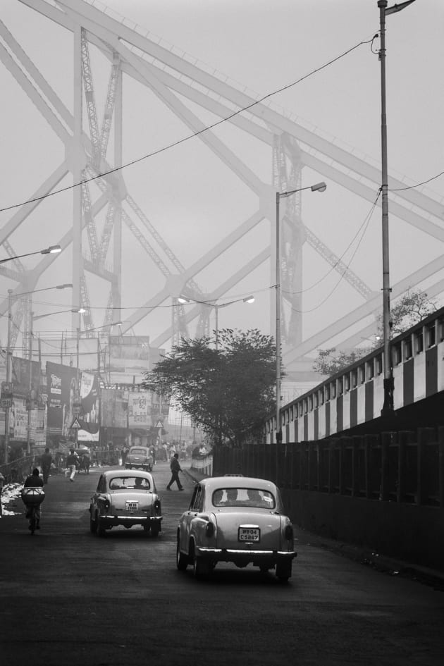 Cold and misty morning by Howrah Bridge in Kolkata, India. The old Classic Ambassadors in black and white really capture the essence of India, in an almost timeless manner. It could have been taken in any era. Canon 6D, Canon 24-105mm f/4 lens @ 88mm. 1/200s @ f4.5, ISO 400, handheld.