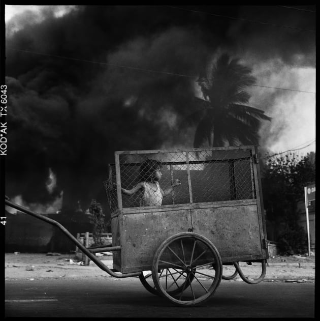 A child is pushed in a cart along the main coastal promenade in Dili as parts of the city go up in flames following the violence and chaos of post referendum for Independence from Indonesia. East Timor, 1999.