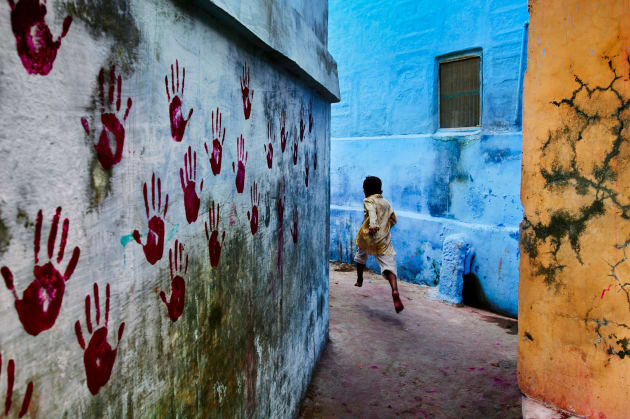 Boy in mid-flight, Jodhpur, India. When visiting a city, McCurry will wander with no set plans or places to visit. It's an approach that allows him to be receptive to any chance event or scene. Copyright Steve McCurry.