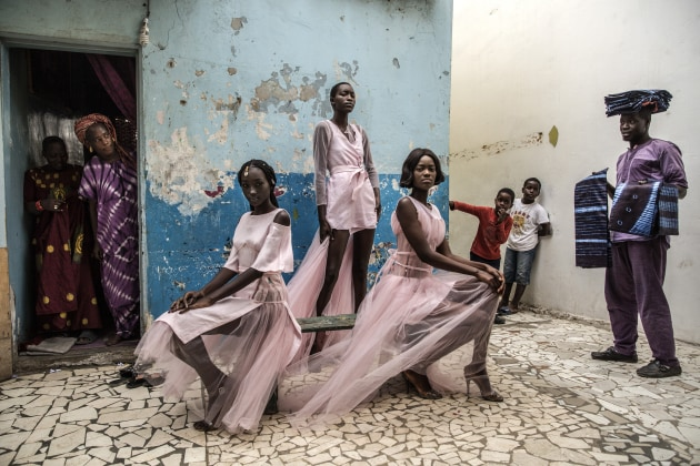 Diarra Ndiaye, Ndeye Fatou Mbaye and Mariza Sakho model outfits by designer Adama Paris, in the Medina neighborhood of the Senegalese capital, Dakar, as curious residents look on. © Finbarr O'Reilly