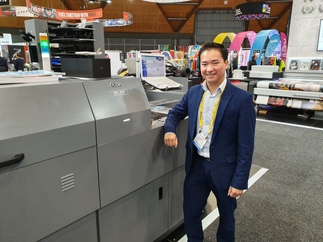 Jimmy Nguyen shows off a Duplo DDC-810 digital spot UV coater on the Neopost stand.