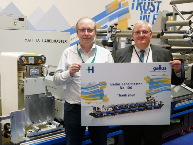 Philippe Carre from Heidelberg France (right) congratulates Christian Linossier from Interfas for his purchase of the hundredth Gallus Labelmaster. (Source: Gallus)