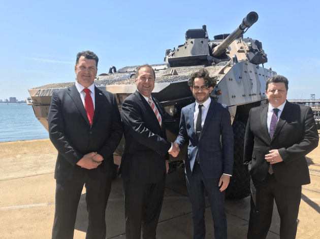 Adam Watson and Brian Gathright from BAE Systems Australia meet with Aidan Butler-Bonnice and Paul Donald of Ruag Australia in front of the AMV35. Credit: Ruag Australia