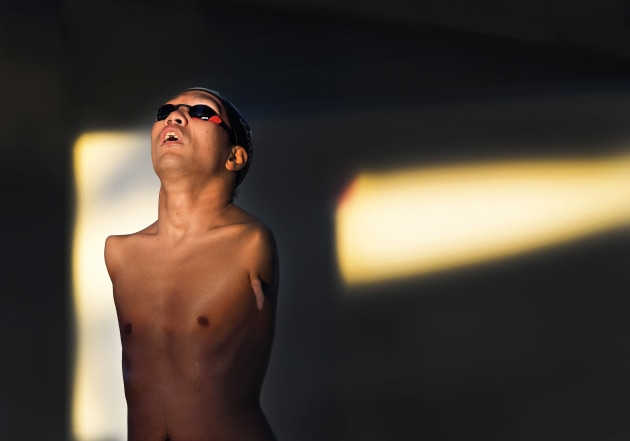 Japanese amputee paralympic swimmer Tomotaro Nakamura looks towards the setting sun and steels himself as he prepares on the block for the start of his S5 50 metre freestyle final at the 2018 Para Pan Pacific Championships at the Tobruk Pool in Cairns Australia. Nakamura, who had both arms amputated below the shoulder at birth, won Gold. He is one of Japans most accomplished paralympic swimmers. Nikon D5, Nikkor 400mm f2.8 lens. 1/1600s @ f5, ISO 800.