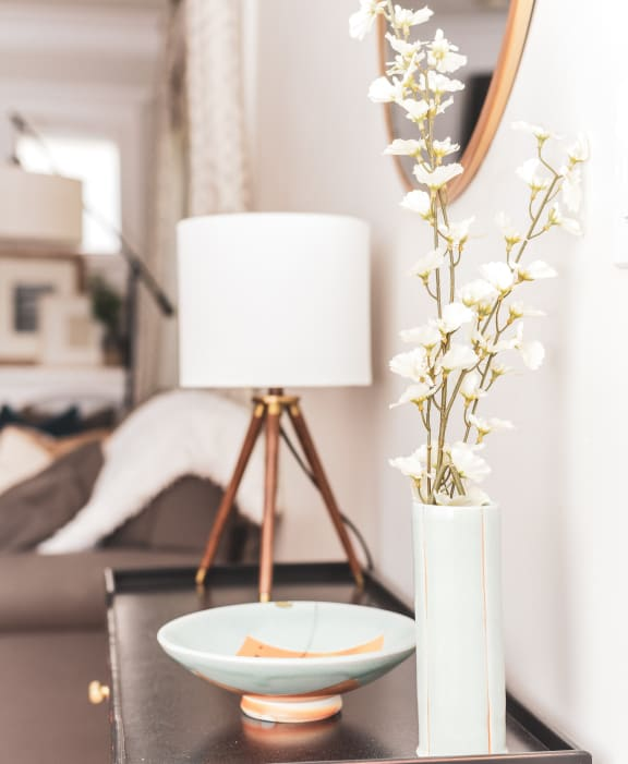 Lamp on end table with small plant and trinkets