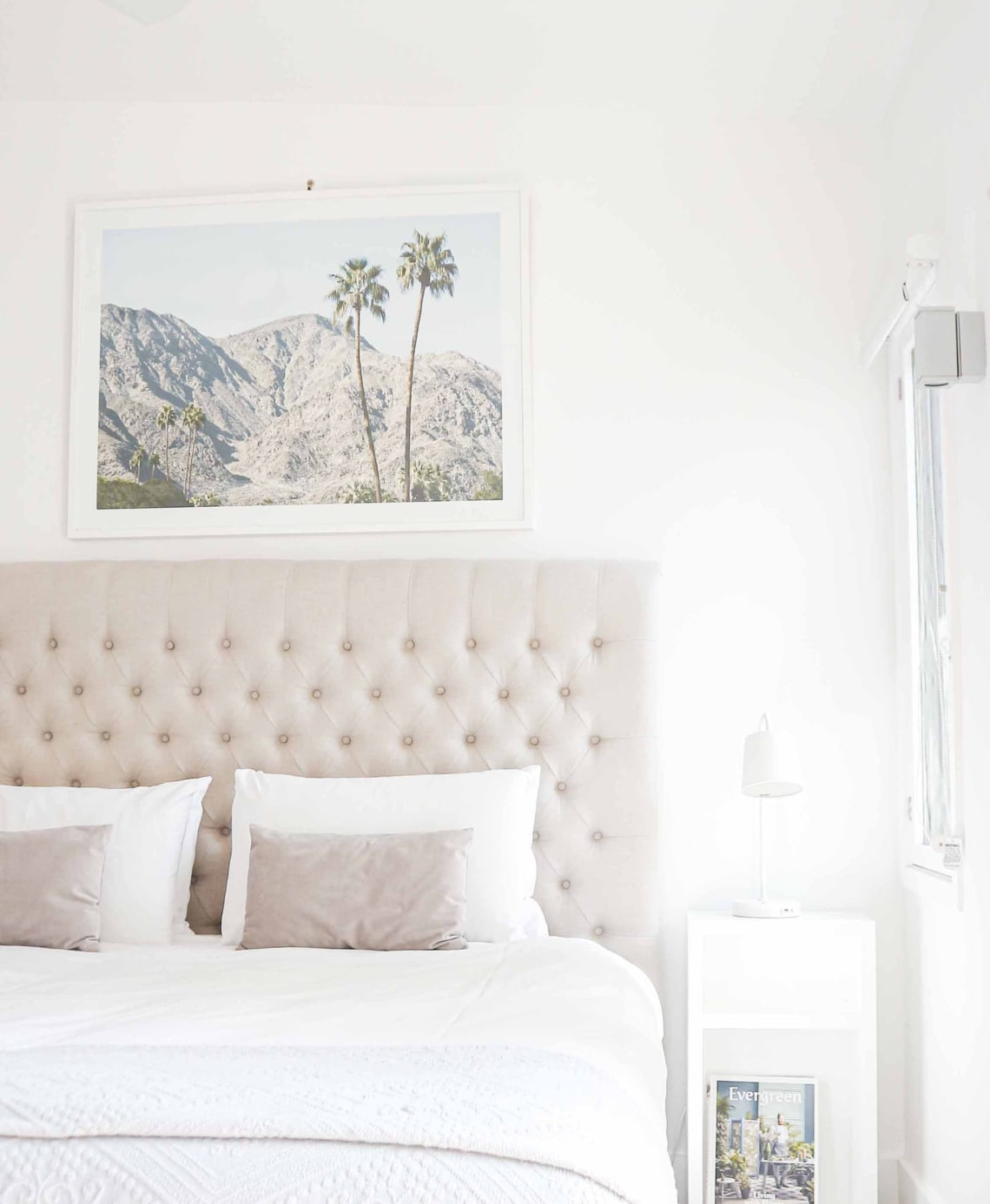 Bedroom with cream headboard and white beading. Photo above bed.